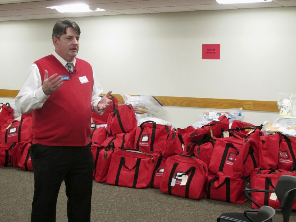 Dane County Clerk Scott McDonell stands in front of sealed bags of ballots before a recount of Wisconsin's presidential election results begins Thursday, Dec. 1, 2016, in Madison, Wis. The first candidate-driven statewide recount of a presidential election in 16 years began Thursday in Wisconsin, a state that Donald Trump won by less than a percentage point over Hillary Clinton after polls long predicted a Clinton victory. (AP Photo/Scott Bauer)