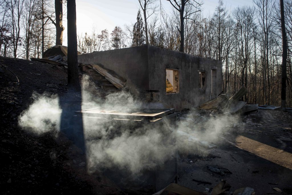 Smoke billows from the remains of a home on the northern outskirts of Gatlinburg, Tenn., on Thursday. (Andrew Nelles/The Tennessean via AP)