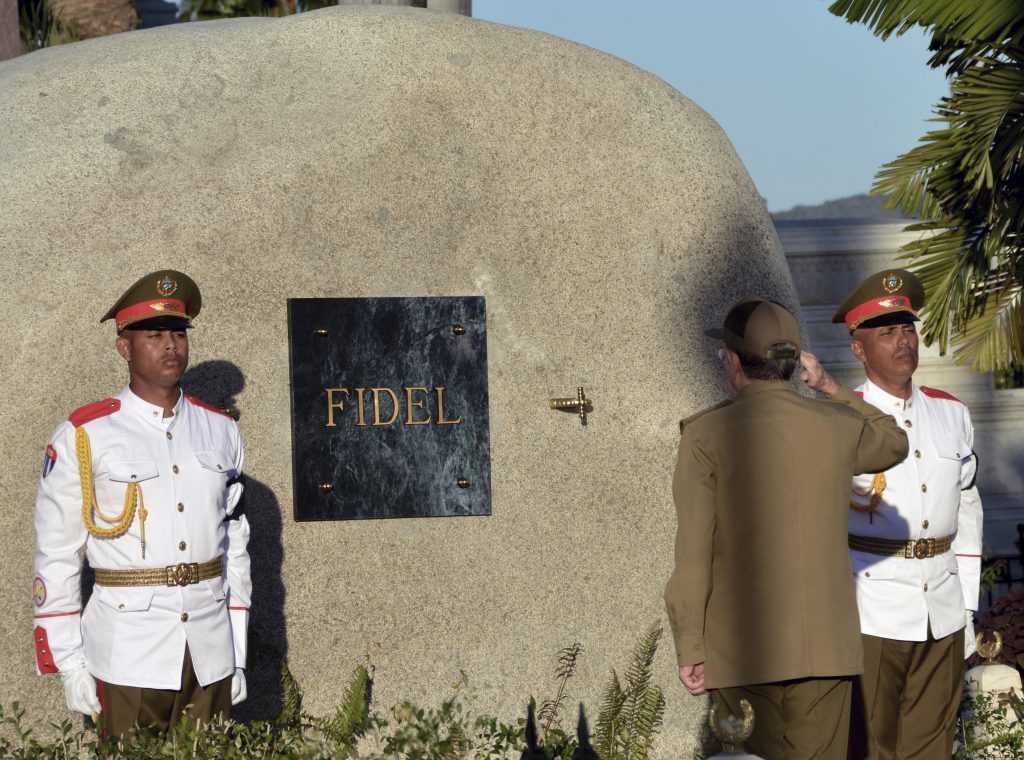 Cuban President Raul Castro salutes at the tomb of his older brother Fidel Castro, at the Santa Ifigenia cemetery in Santiago, Cuba, on Sunday. (Marcelino Vazquez Hernandez/ACN via AP)