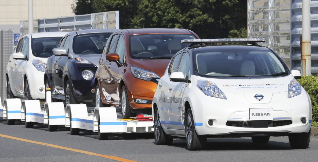 "Nissan Motor Co.'S ""Leaf"", with no one inside, pulls a trailer with three other Leafs on it, during a demonstration of the automaker's Intelligent Vehicle Towing system at Nissan Oppama plant in Yokohama, near Tokyo Monday, Dec. 5, 2016. Nissan Motor Co. is testing out self-driving cars at one of its plants in Japan to tow vehicles on a trailer to the wharf for loading without anyone behind the steering wheel. (AP Photo/Koji Sasahara)"