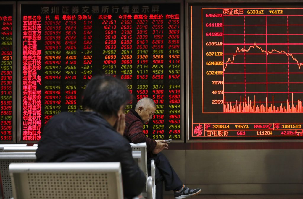 An investor browses his smartphone as another looks at an electronic board displaying stock prices at a brokerage house in Beijing, Monday, Dec. 5, 2016. Asian shares tumbled Monday after Italian voters' rejected constitutional changes, raising questions over whether Italy will stay in the European Union and keep using the euro. (AP Photo/Andy Wong)
