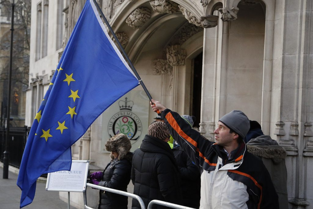 A man waves a European flag in front of the Supreme Court in London, Monday, Dec. 5, 2016. May's government will ask Supreme Court justices to overturn a ruling that Parliament must hold a vote before Britain's exit negotiations can begin _ a case that has raised a constitutional quandary and inflamed the country's heated debate about Brexit. (AP Photo/Frank Augstein)