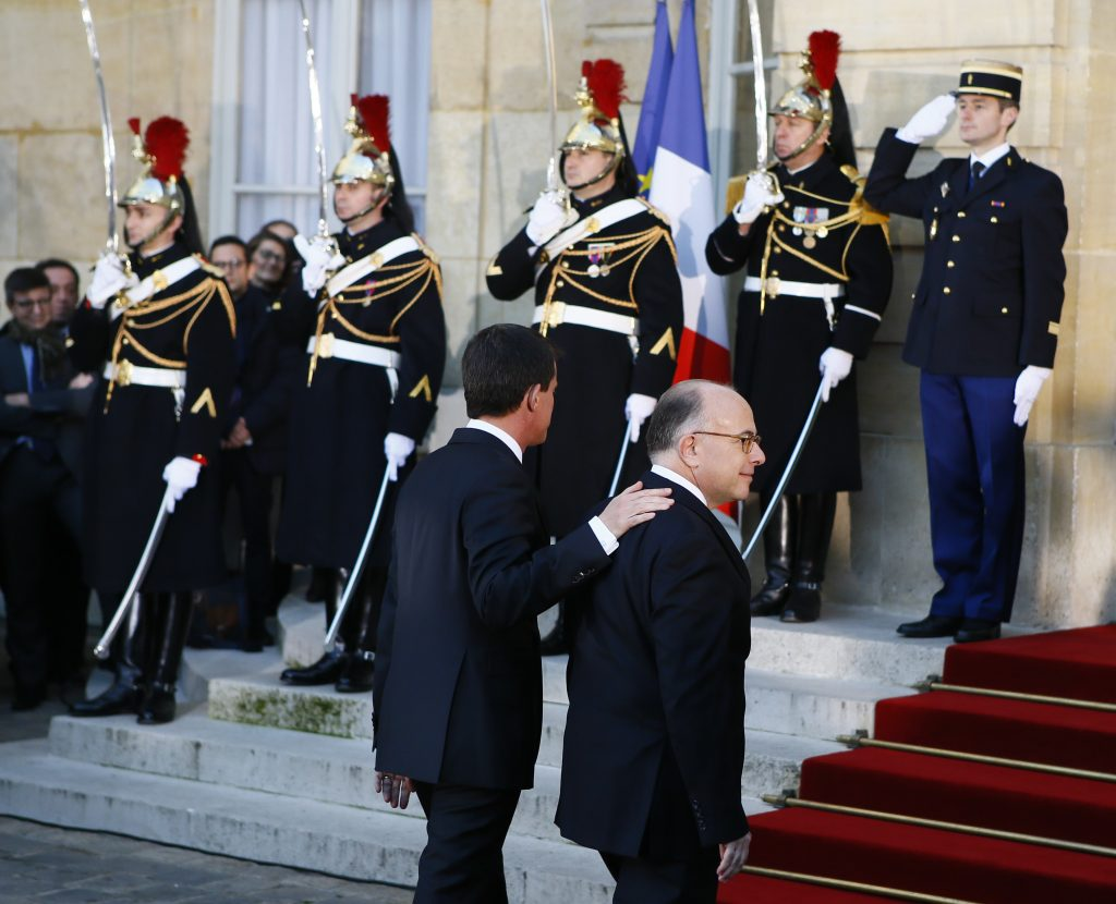 Outgoing Prime Minister Manuel Valls, left, welcomes Interior Minister Bernard Cazeneuve before the hand over ceremony in Paris, Tuesday, dec.6, 2016. Valls stepped down Tuesday to focus on running for president in next year's election and was replaced by Interior Minister Bernard Cazeneuve, a man who embodies the fight against Islamic extremism. (AP Photo/Francois Mori)