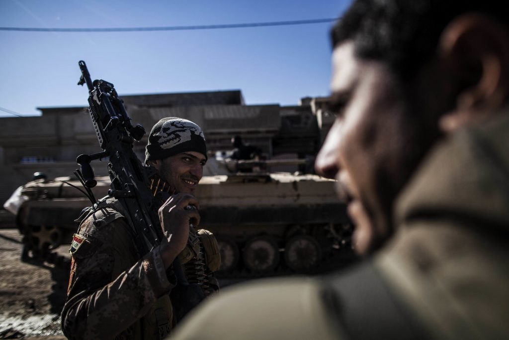 An Iraqi soldier from the 9th Infantry Division holds his machine gun while heading to the frontline in Shyma district in Mosul, Iraq, Tuesday, Dec. 6, 2016. Iraqi forces, backed the U.S.-led international coalition, launched a campaign in October to retake Mosul, the country's second largest city and IS's last major urban bastion in Iraq. (AP Photo/Manu Brabo)