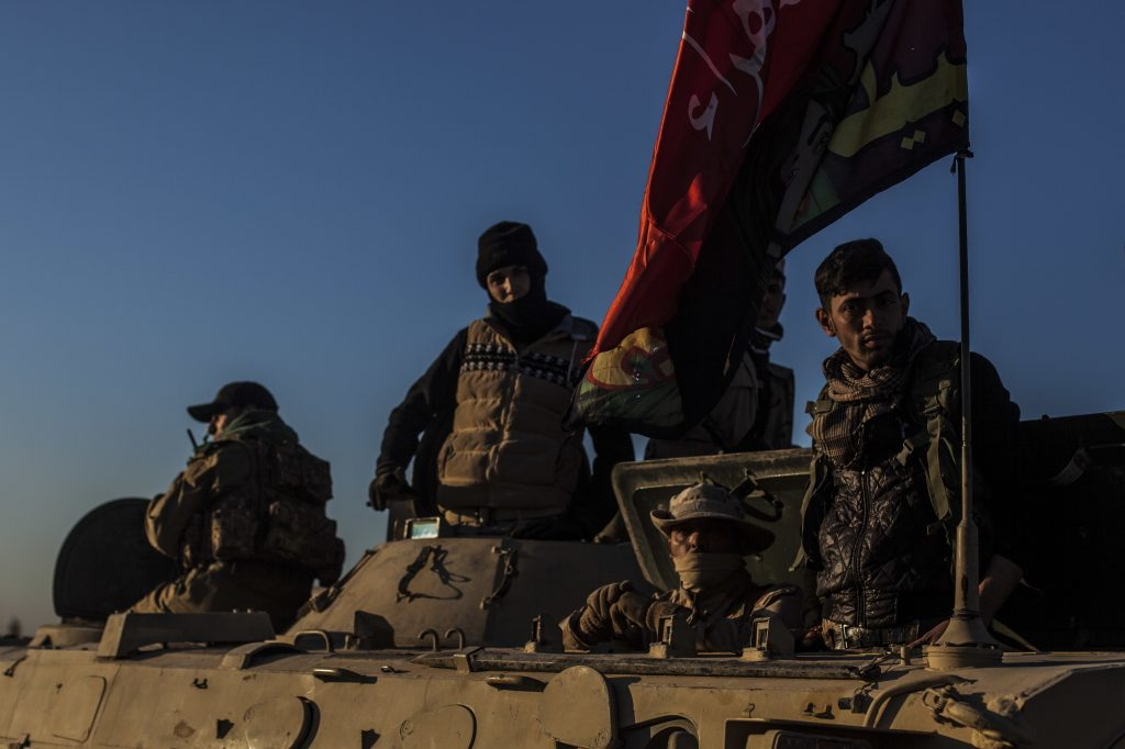 Iraqi Army soldiers are seen atop an armored vehicle  at the outskirts of Mosul while waiting to go to the front lines, on Tuesday.  (AP Photo/Manu Brabo)