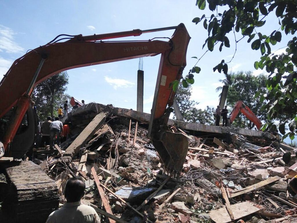 Rescuers use heavy machine to search for survivors under the rubble of a collapsed building after an earthquake in Pidie Jaya, Aceh province, Indonesia, Wednesday, Dec. 7, 2016. A strong undersea earthquake rocked Indonesia's Aceh province early on Wednesday, killing at a number of people and causing dozens of buildings to collapse. (AP Photo/Heri Juanda)