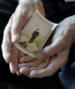 Earl Wanbaugh, 98, holds a photo of himself as a young sailor. (John Sleezer/The Kansas City Star via AP)