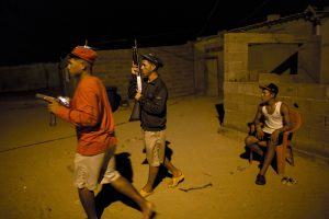 """Members of the Marval family, who patrol at night while other members of their family fish at sea, respond to what appeared to be the start of an attack by pirate gang leader """"El Beta"""" in Punta de Araya, Sucre state, Venezuela. (AP Photo/Rodrigo Abd)"""