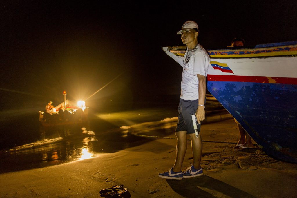 """A member of the Marval fishing family who goes by the nickname """"El Chukiti"""" holds a homemade gun as he guards against a possible pirate attack as fishermen unload their catch in Punta de Araya, Sucre state, Venezuela, in November. (AP Photo/Rodrigo Abd)"""