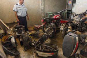 A municipal police officer stands amid stolen engines seized from pirates, at the police station in Punta de Araya, Venezuela. (AP Photo/Rodrigo Abd)