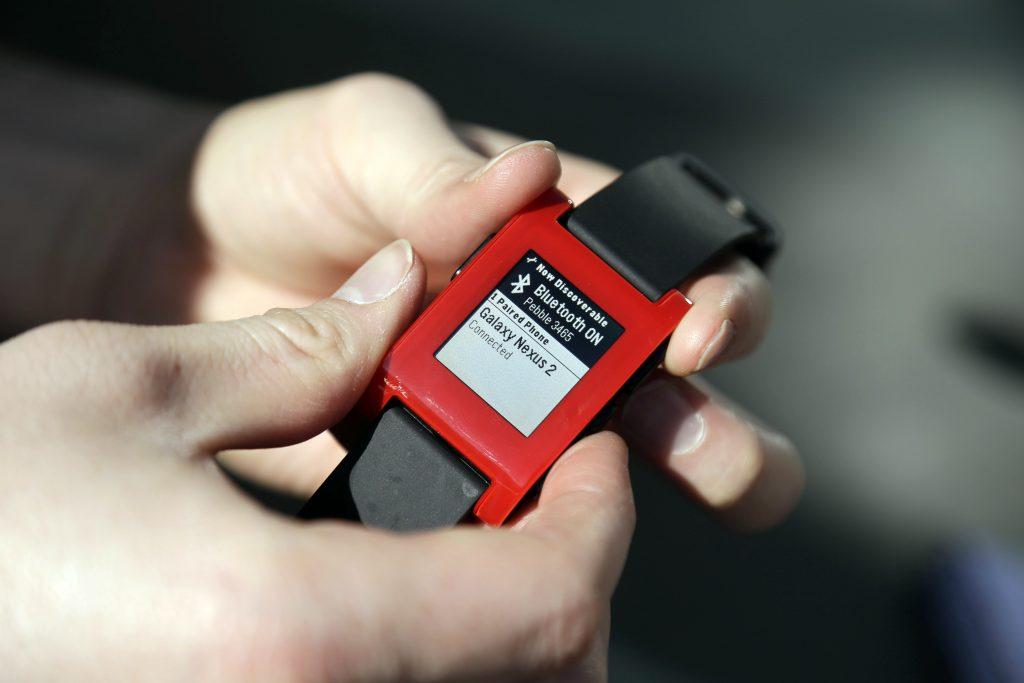 Eric Migicovsky, CEO of Pebble, displaying his company's smartwatch in 2013. (AP Photo/Marcio Jose Sanchez, File)
