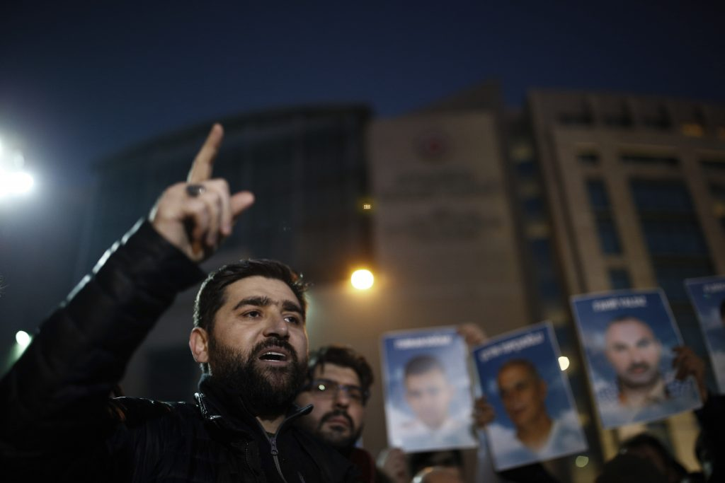 Pro-Islamic activist Adem Ozkose gestures as family members hold up photos of victims of the Mavi Marmara ship, the lead boat of a flotilla headed to the Gaza Strip, which was stormed by Israeli naval commandos in a predawn confrontation, outside the city's main courthouse after the trial in Istanbul, Friday, Dec. 9, 2016. Turkey's state-run Anadolu Agency says a court has dropped a case against Israeli military officials accused over the deaths of 10 Turkish activists, a decision aligned with a reconciliation pact between Turkey and Israel. (AP Photo/ Emrah Gurel)