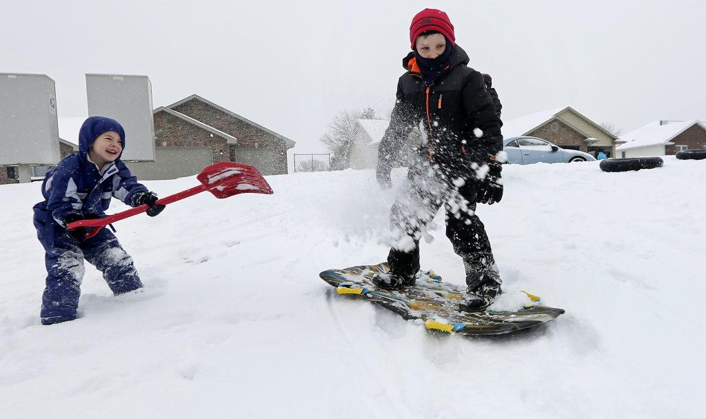 Austin Ricks, 4, and Brandon Grimes, 9, play in the snow in Asbury, Iowa, on Sunday. (Nicki Kohl/Telegraph Herald via AP)
