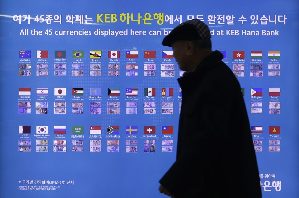 A man walks by a board displaying various banknotes issued in the world at a subway station in Seoul, South Korea, Thursday, Dec. 15, 2016. Share benchmarks in Asia are seeing moderate losses early Thursday, after the Federal Reserve raised interest rates overnight. The quarter percentage point rate increase, the second in a decade, was widely expected although investors were surprised to see the Fed project three more increases for 2017. (AP Photo/Ahn Young-joon)