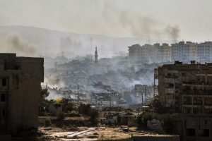 In this photo released by the Syrian official news agency SANA, smoke rises in an east Aleppo neighborhood in Syria, Thursday, Dec. 15, 2016. Syrian activists said residents in eastern Aleppo are starting to board buses and ambulances, the first step in an evacuation that is part of the rebel enclave's effective surrender. (SANA via AP)
