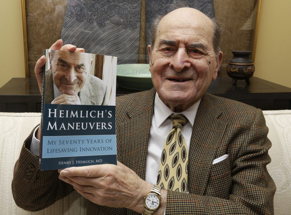 FILE - In this Feb. 5, 2014, file photo, Dr. Henry Heimlich holds his memoir prior to being interviewed at his home in Cincinnati. Heimlich, the surgeon who created the life-saving Heimlich maneuver for choking victims has died Saturday, Dec. 17, 2016, at Christ Hospital in Cincinnati. He was 96. (AP Photo/Al Behrman, File)