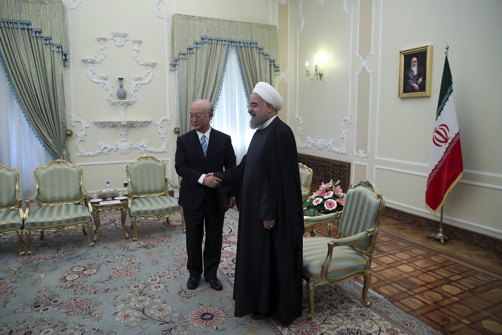 In this photo released by official website of the office of the Iranian Presidency, President Hassan Rouhani, right, and Director General of the International Atomic Energy Agency, IAEA, Yukiya Amano shake hands for media at the start of their meeting at Presidency office in Tehran, Iran, Sunday, Dec. 18, 2016. (Iranian Presidency Office via AP)