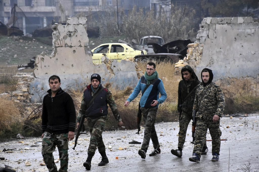 This photo released by the Syrian official news agency SANA, shows Syrian troops and pro-government gunmen marching through the streets of east Aleppo on Tuesday. (SANA via AP)