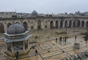 Syrian troops and pro-government gunmen marching inside the destroyed Grand Umayyad mosque in the old city of Aleppo on Tuesday. (SANA via AP)