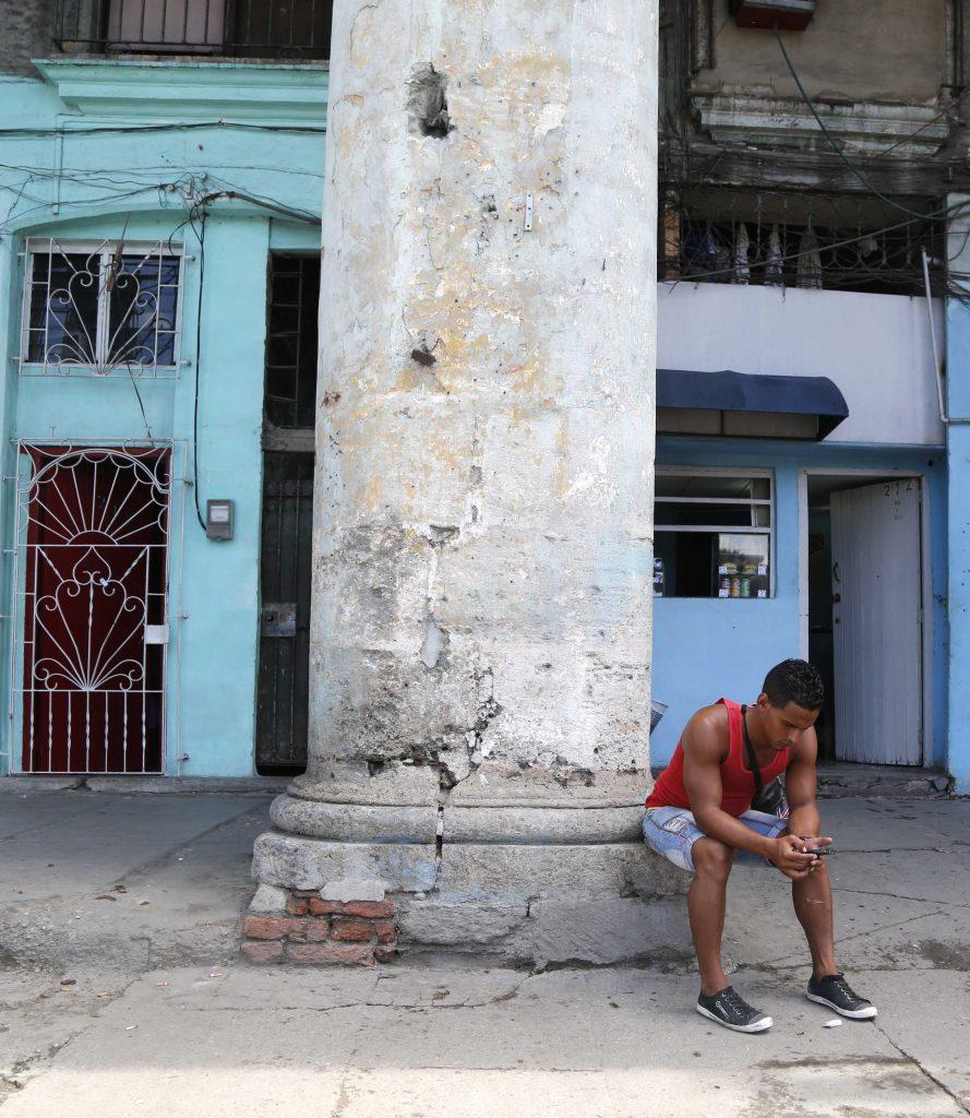A youth uses his smartphone in Havana. (AP Photo/Desmond Boylan)
