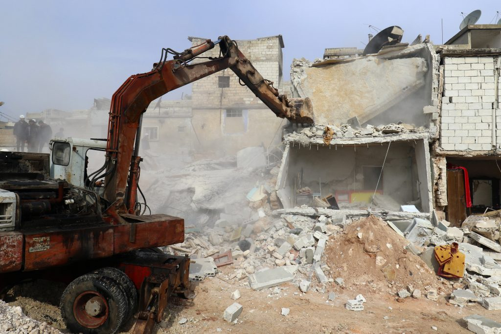 An excavator removes rubble of damaged buildings after air strikes on the northern neighbourhood of Idlib city, Syria December 5, 2016. REUTERS/Ammar Abdullah