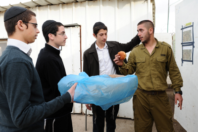 Orthodox Chabad offer an Israeli soldier a 'sufganiya', traditionally eaten for the Jewish holiday of Hanukkah, in the West Bank city of Hebron. The Hanukkah festival is observed by the kindling of the lights of a 'hanuckia'- a nine-branched candelabrum, with one additional light being lit on each night of the holiday. November 29, 2013. Photo by Mendy Hechtman/Flash90 *** Local Caption *** ??????? ????? ????? ????
