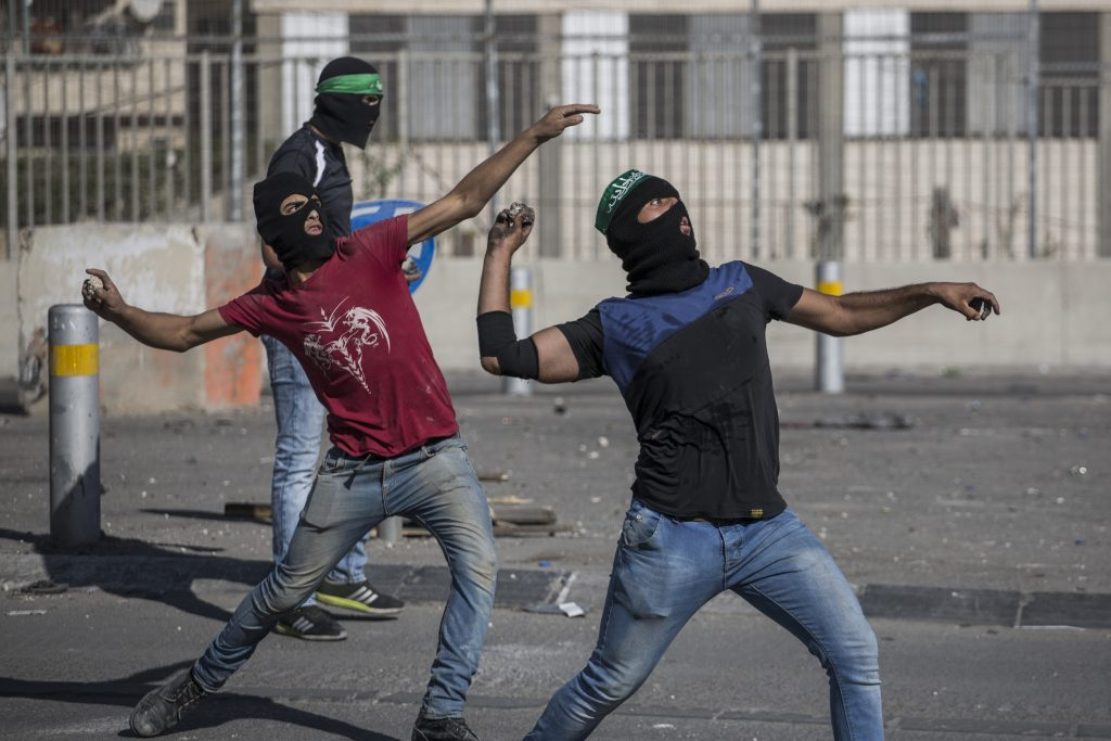 Palestinian youth throw rocks at Israeli Border Police during clashes at the Shuafat Refugee Camp in 2015. (Hadas Parush/Flash90)