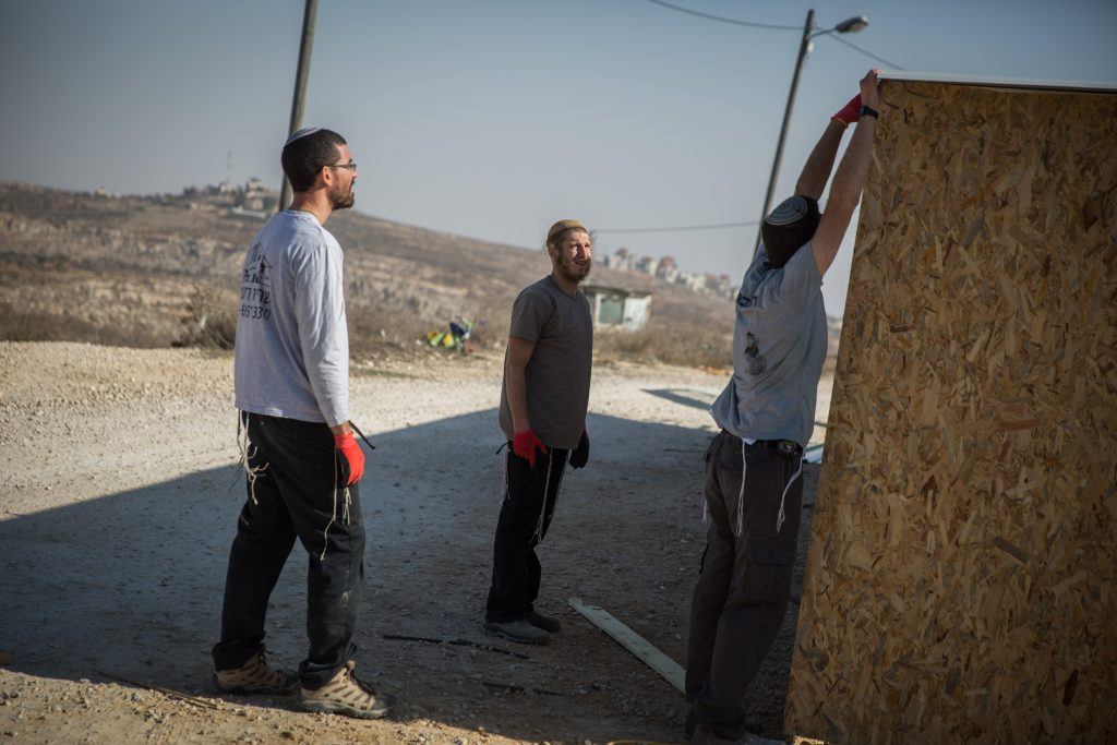 Young Jewish men seen building a structure in the Jewish settlement of Amona in the West Bank, on November 28, 2016. The structure is meant to house supporters for when the state decides to evacuate the illegal settlement. Photo by Hadas Parush/Flash90 *** Local Caption *** בנייה עמונה פינוי התנחלות יהודים צעירים בונים