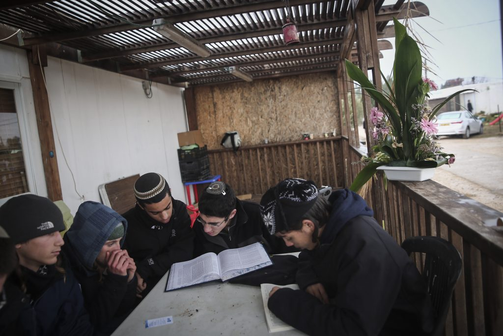 Young boys study Torah in the Jewish settlement of Amona in the West Bank, on December 18, 2016. Amona is an illegal Jewish settlement on private Palestinian owned land and is set to be evacuated. Photo by Miriam Alster/Flash90 *** Local Caption *** בנייה עמונה פינוי התנחלות יהודים מתפלל בוקר