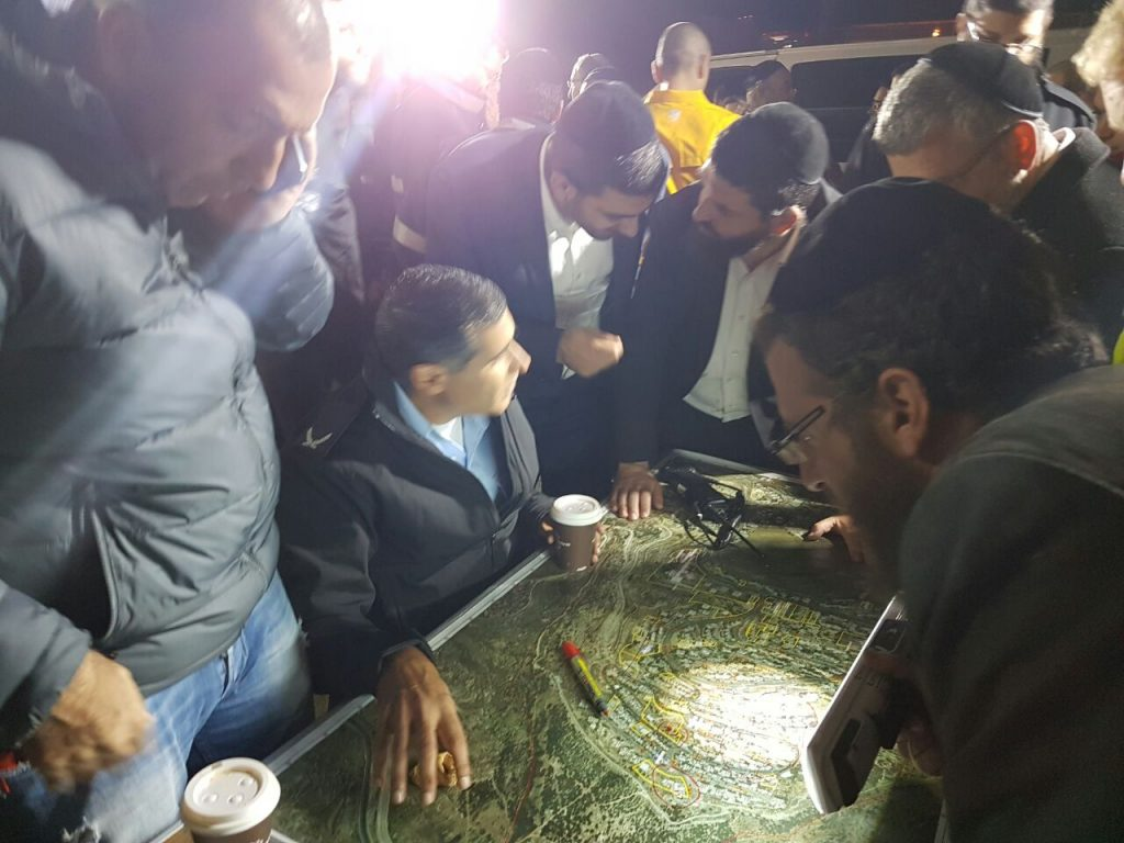 Volunteers and police pore over maps in the search of the missing boy Sunday night. (ZAKA)