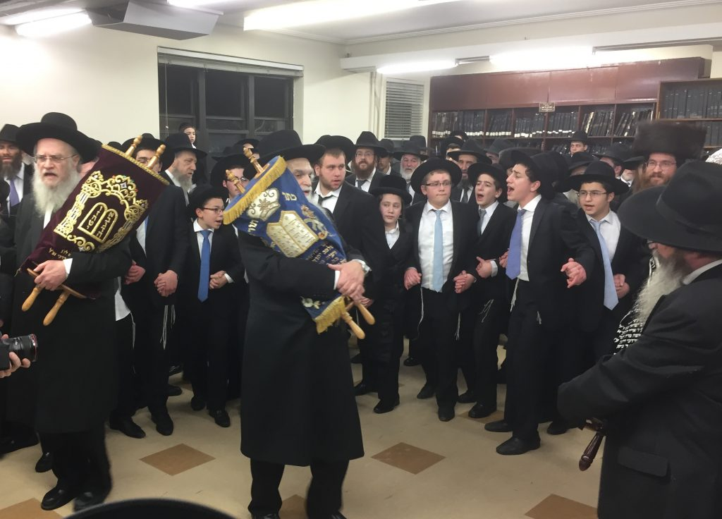 Rabbi Mendel Bromberg dancing in the center of the circle. The new Sefer Torah was donated by Mr. Adelsburg l'iluy nishmas Rabbi Bromberg's parents and parents-in-law. At left is his brother, Harav Avraham Bromberg. (Isser Berg/Hamodia) and Harav Avraham Bromberg (L) center