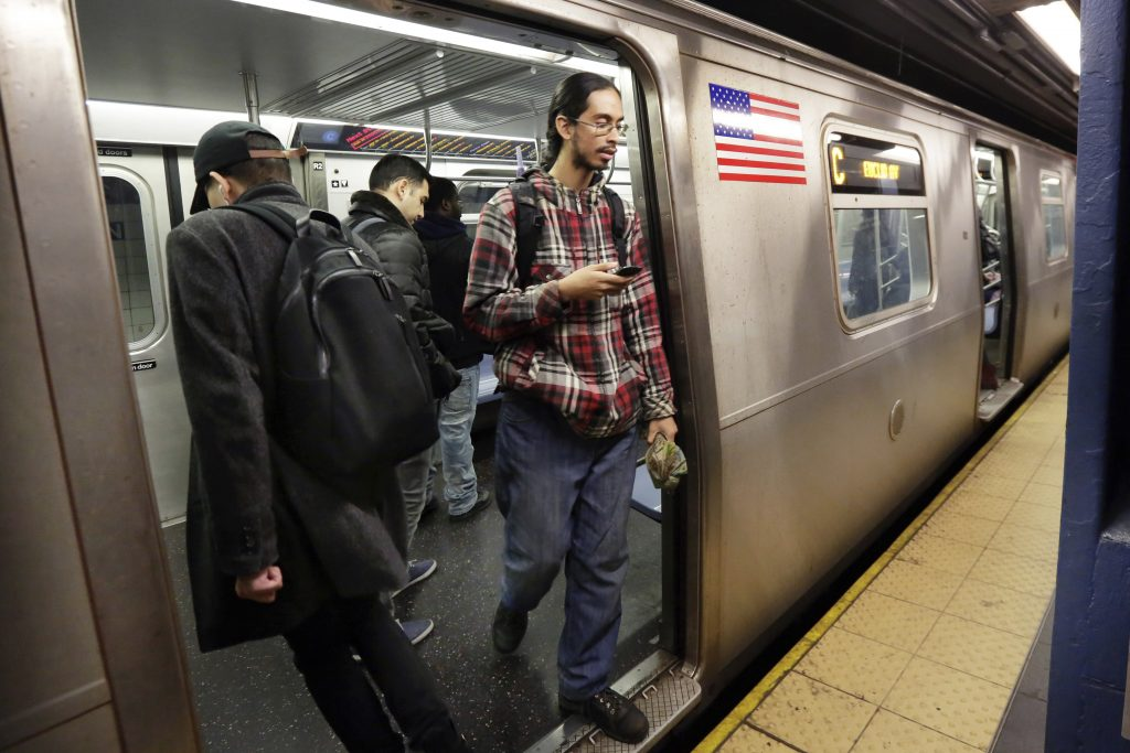 Samuel Santaella, a low-income resident of Queens, steps from a subway car Wednesday.(AP Photo/Richard Drew)