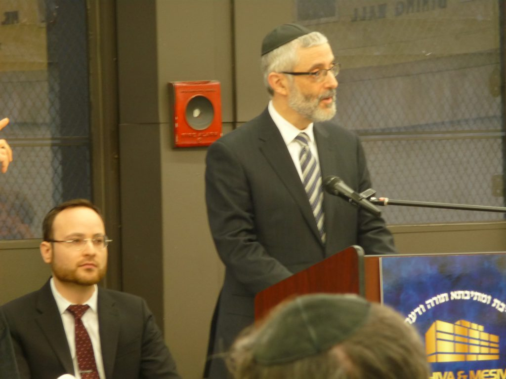 Rabbi Chaim Dovid Zwiebel, Agudath Israel's Executive Vice President, speaks at the NYC Yeshiva Conference. Mr. Avrohom Weinstock, the organization's Associate Director of Education Affairs, is on the left.