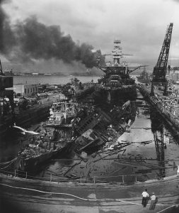 The wrecked destroyers USS Downes and USS Cassin in Drydock One at the Pearl Harbor Navy Yard, soon after the end of the Japanese air attack. Cassin has capsized against Downes. USS Pennsylvania is astern, occupying the rest of the drydock. The torpedo-damaged cruiser USS Helena is in the right distance, beyond the crane. Visible in the center distance is the capsized USS Oklahoma, with USS Maryland alongside. The smoke is from the sunken and burning USS Arizona, out of view behind Pennsylvania. USS California is partially visible at the extreme left. This photo was taken by acclaimed Navy photographer Harold  Fawcett, who captured many memorable photos of the attack at Pearl Harbor.