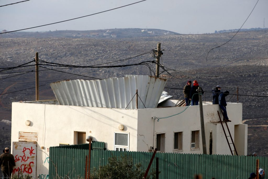 Jewish youths stand atop a roof in the Jewish settler outpost of Amona in the West Bank December 18, 2016. REUTERS/Baz Ratner