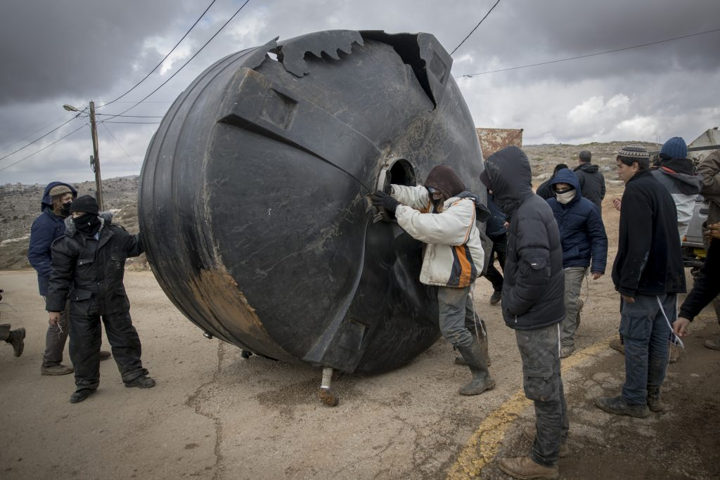 Young people move obstacles into place on Thursday, in preparation of resisting the Amona evacuation. (Yonatan Sindel/Flash90)
