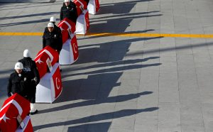 Turkish police officers stand by coffins of fellow officers who died in Saturday's blasts during a ceremony at the police headquarters in Istanbul on Sunday. (Reuters/Murad Sezer)