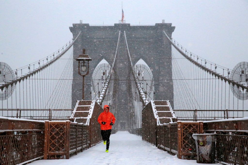 A man runs over the Brooklyn Bridge during morning snow in Manhattan, New York City, U.S. December 17, 2016. REUTERS/Andrew Kelly TPX IMAGES OF THE DAY