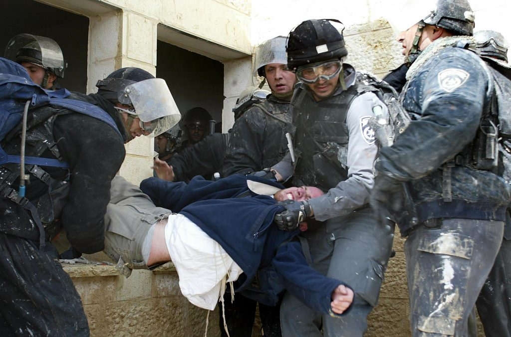Injured settlers are arrested by Israeli policemen during clashes in the West Bank settlement of Amona Jan. 1, 2006. Hundreds of Jewish hardliners were dragged kicking and screaming out of houses in the occupied West Bank as Israeli security forces stormed the unauthorized settlement. Rocks and paint were hurled at the massed ranks of the border police as they moved in to clear out hundreds of settlers who had barricaded themselves inside and on the roofs of nine houses in the settlement outpost near the Palestinian city of Ramallah. Photo by Pierre Terdjman/Flash90. *** Local Caption *** ????? ????? ????? ??????? ????? ?????? ?????? ??????? ??????? ???????? ??????? ???????? ???????? ????????? ???????? ?????????