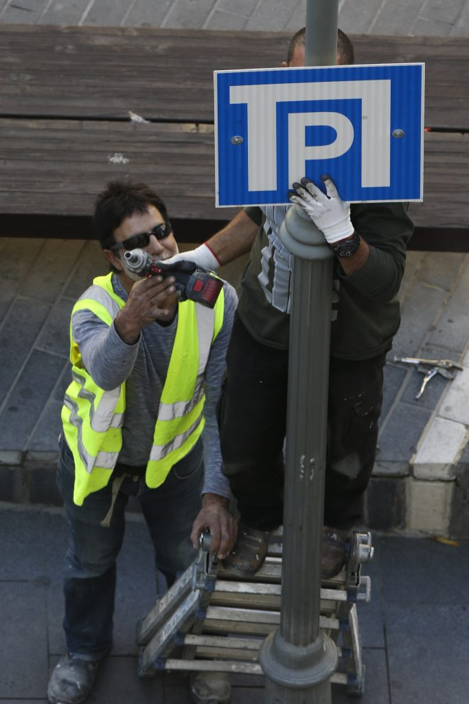 Jerusalem municipality workers put up parking signs on a street in downtown Jerusalem. November 19, 2014. photo by Nati Shohat/FLASH90 *** Local Caption *** שלט חניה תמרור