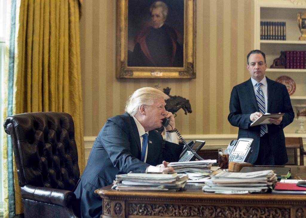 President Donald Trump, accompanied by Chief of Staff Reince Priebus speaks on the phone with Russian President Vladimir Putin