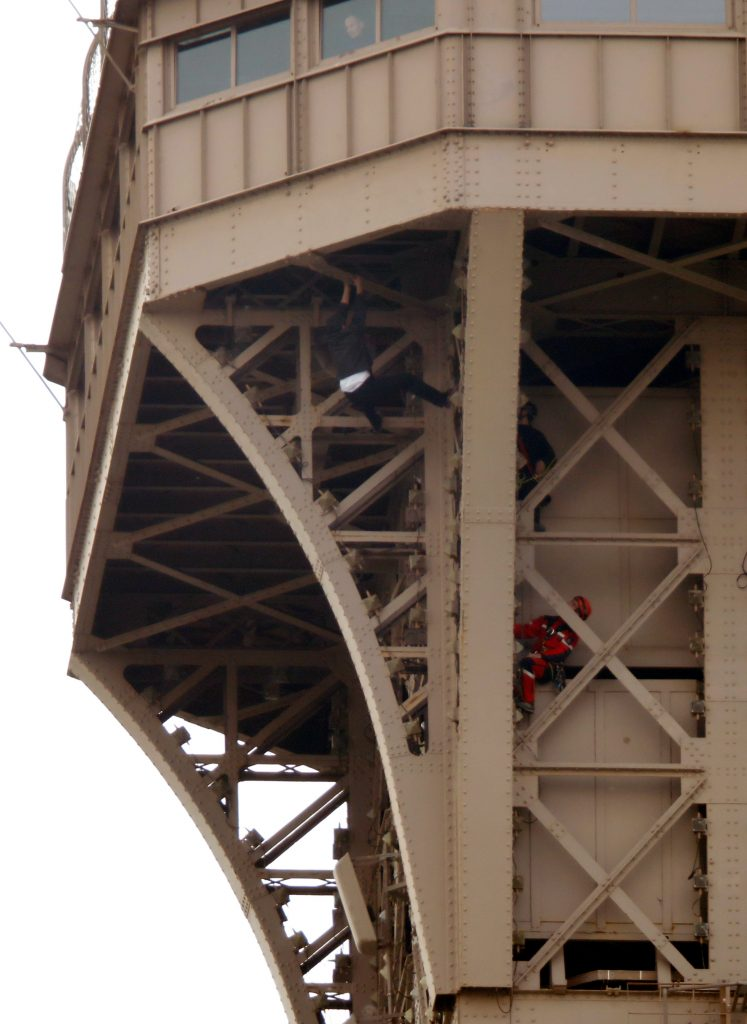 man climbs eiffel tower